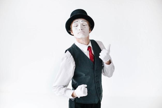 Mimo en sombrero negro y chaleco danzas sobre fondo blanco Foto gratis