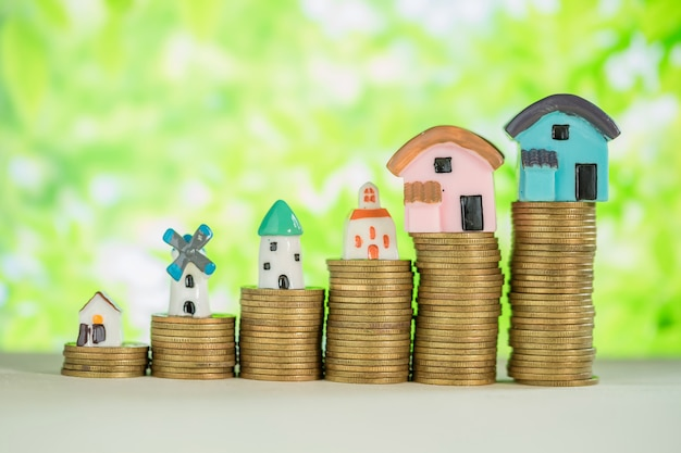 Mini casa en pila de monedas con desenfoque verde. Foto gratis