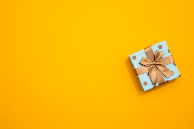 Minimalista envuelto regalo sobre fondo amarillo Foto gratis