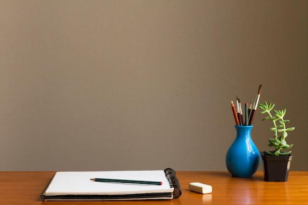 Minimalista espacio de trabajo con bocetos y pinceles artísticos. Foto gratis