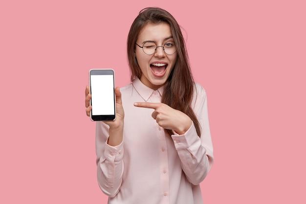 ¡mira este celular! la mujer feliz y complacida parpadea los ojos, señala con el dedo índice a la pantalla en blanco, muestra un dispositivo moderno Foto gratis