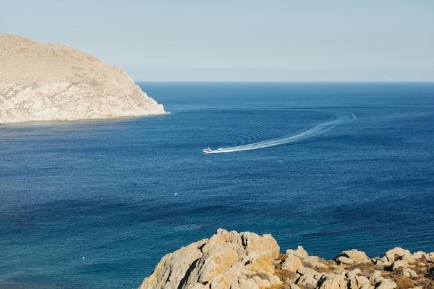 Mira desde lejos el barco que cruza el mar en algún lugar de grecia. Foto gratis