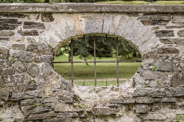 Mirilla con barras de hierro en una valla de piedra Foto gratis
