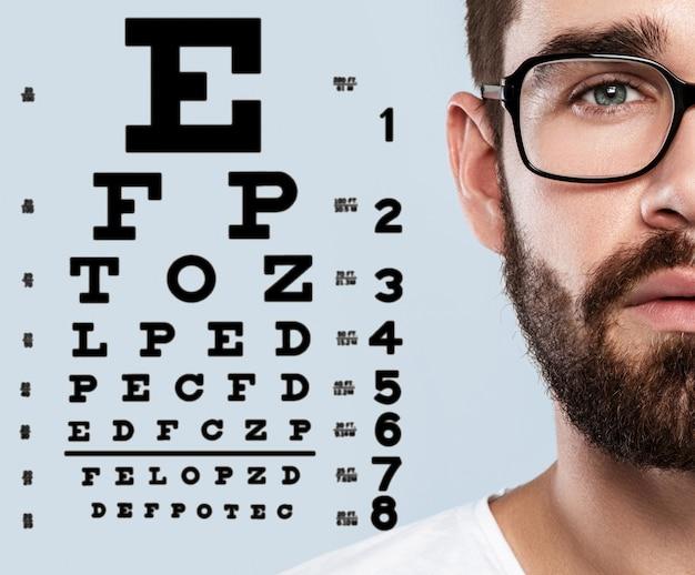 La mitad del rostro masculino y la tabla optométrica Foto Premium