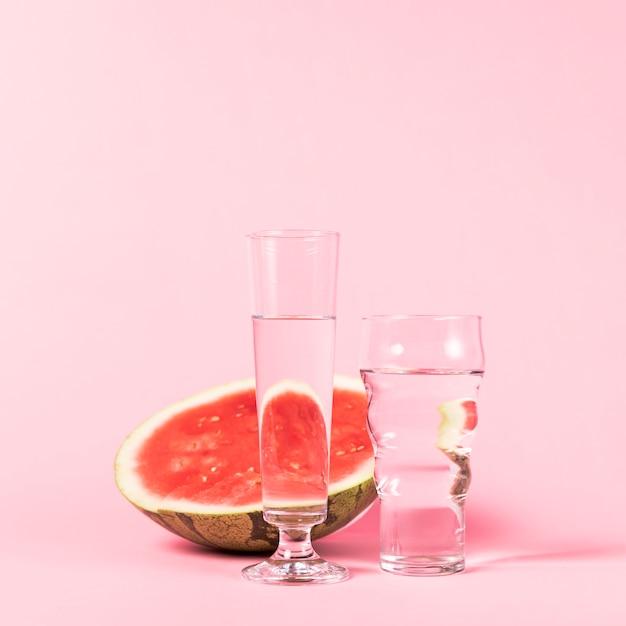La mitad de sandía y vasos con agua. Foto gratis