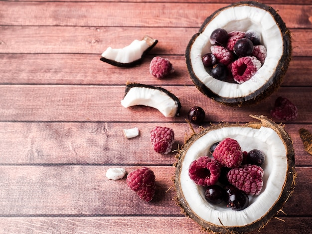 Mitades de coco con bayas congeladas sobre un fondo de madera oscuro Foto Premium