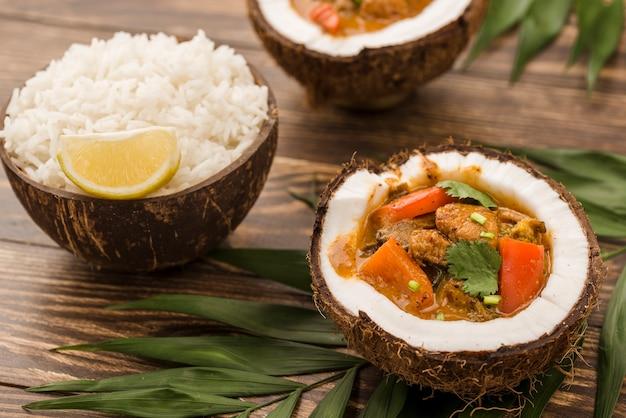 Mitades de coco con estofado y arroz Foto gratis