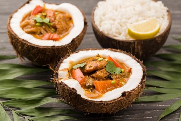 Mitades de coco rellenas de estofado vista alta Foto gratis