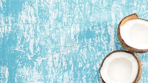 Mitades de fruta de coco sobre fondo azul. Foto gratis