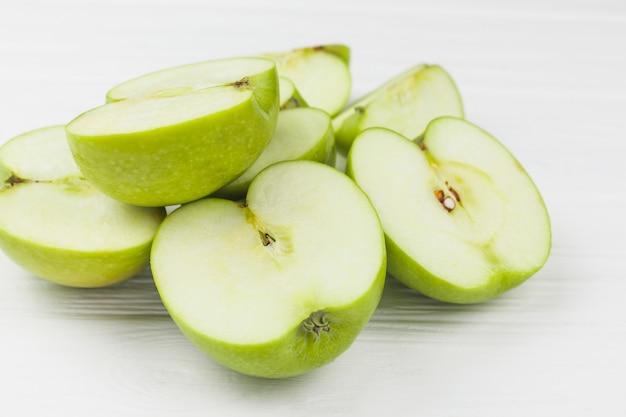 Mitades de manzanas jugosas en mesa blanca Foto gratis