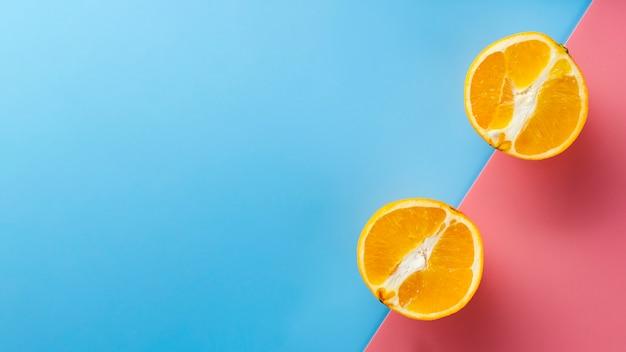 Mitades de naranja sobre fondo de color Foto gratis