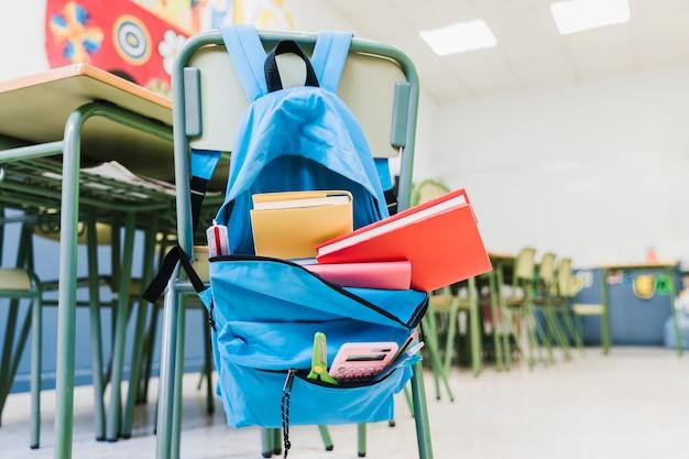 Mochila escolar con libros de texto en silla. Foto gratis