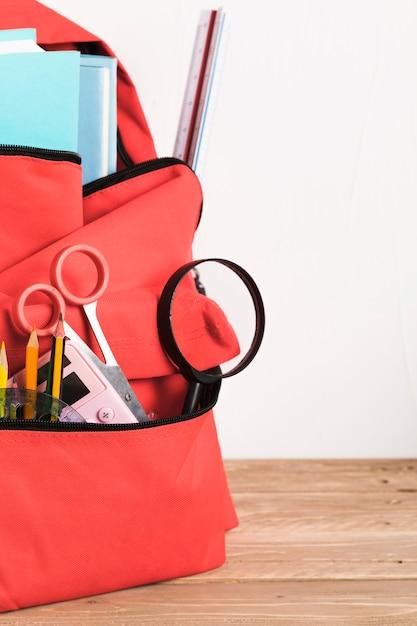 Mochila escolar roja con suministros esenciales. Foto gratis