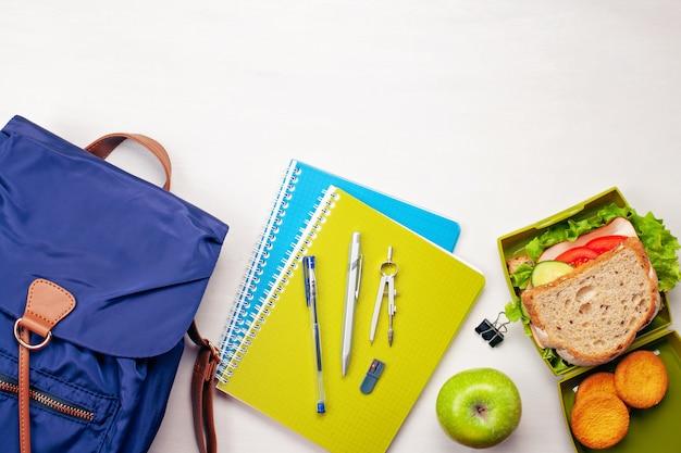 Mochila de estudiante, útiles escolares y bocadillo fresco. Foto Premium