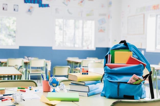 Mochila con libros y papelería dispersa en escritorio. Foto gratis