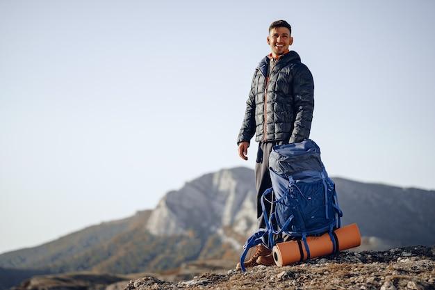 Mochilero masculino en equipo de senderismo de pie en la cima de la montaña Foto Premium