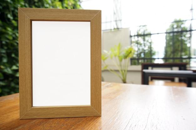 Mock up marco blanco en pie de pie en la mesa de madera en el ...
