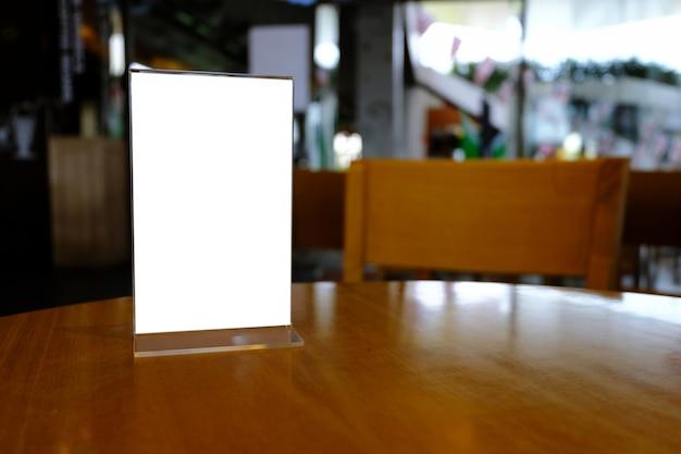 Mock up marco de menú de pie en la mesa de madera en el café del ...