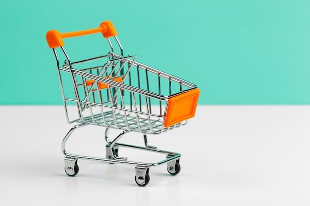 Mock up shoppong carro en línea en la mesa de escritorio de la oficina de pared azul suave Foto Premium