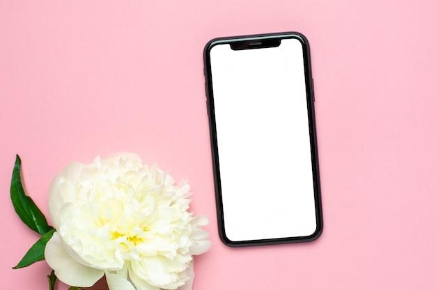 Mock up de teléfono móvil y flor de peonía en rosa pastel mesa. escritorio de trabajo de mujer. color de verano Foto Premium