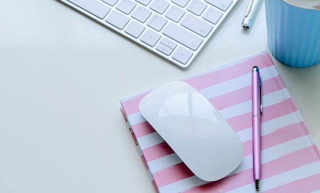 Mockup compute mouse y bolígrafo en el cuaderno con teclado de computadora y taza en la mesa superior blanca. Foto Premium