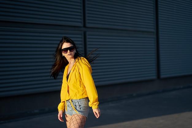 Moda Elegante Chica Morena Inconformista Vestida Con Chaqueta Amarilla Juvenil Pantalones Cortos De Mezclilla Y Gafas De Sol De Moda Posando En Una Pared Urbana De Metal Gris Foto Premium
