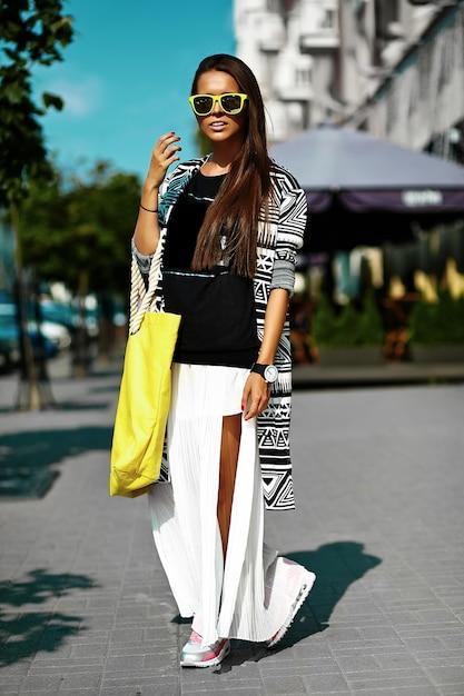 Moda elegante hermosa morena joven modelo en verano hipster ropa casual colorida posando en el fondo de la calle Foto gratis