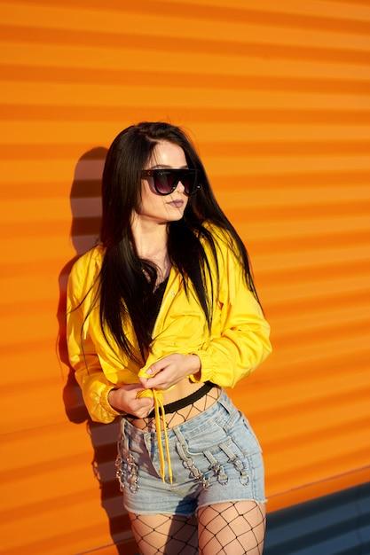 Moda Joven Linda Con Elegante Chaqueta Amarilla Juvenil Pantalones Cortos De Mezclilla Y Gafas De Sol Posando Sobre Fondo Naranja Pared Urbana Foto Premium