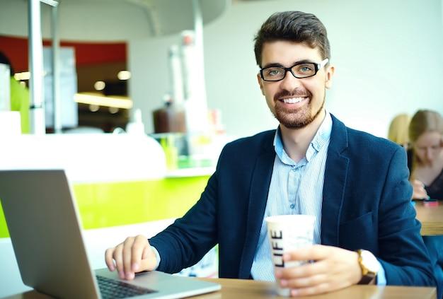 Moda joven sonriente hipster hombre tomando café en la cafetería de la ciudad durante la hora del almuerzo con cuaderno en traje Foto gratis