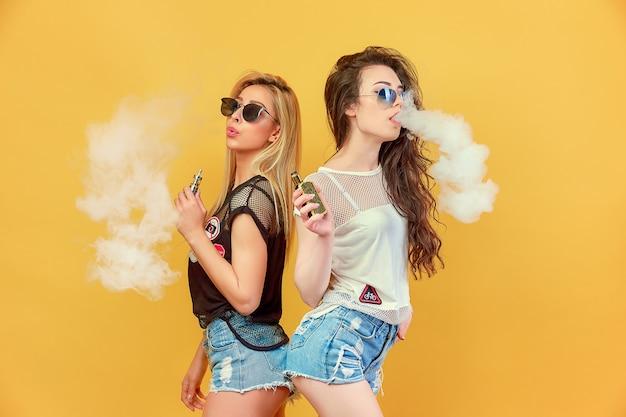 Moda Jovenes Amigos En Gafas De Sol Y Pantalones Cortos De Pie Y Fumando Foto Premium