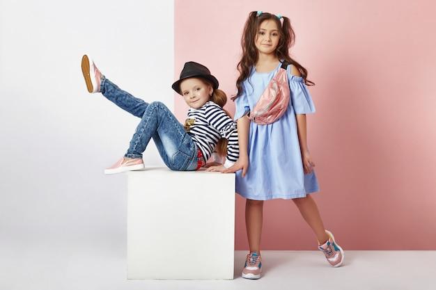 Moda niño y niña en ropa elegante en la pared de color b Foto Premium