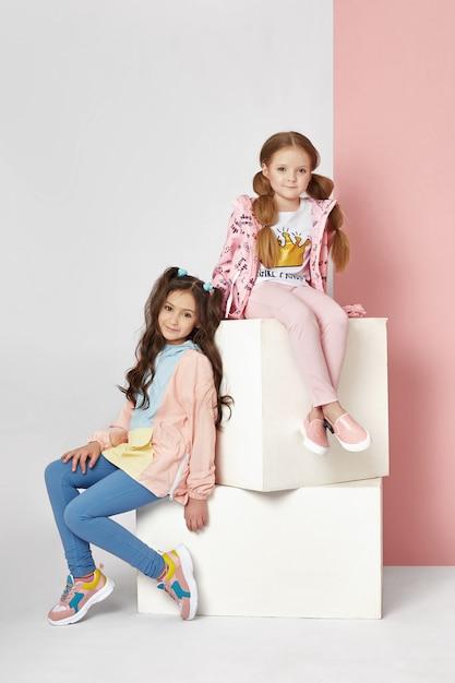 Moda niño y niña en ropa elegante en pared de color Foto Premium