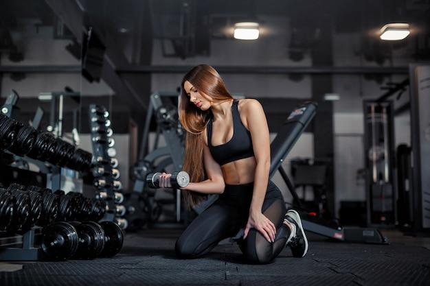 Modelo adulto joven de la muchacha que hace levantamiento de pesas en el gimnasio que se sienta cerca del espejo Foto Premium