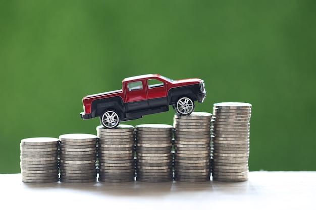 Modelo de automóvil en miniatura en la creciente pila de dinero de monedas sobre fondo verde de la naturaleza, ahorro de dinero para automóvil, finanzas y préstamo de automóvil, inversión y concepto empresarial Foto Premium