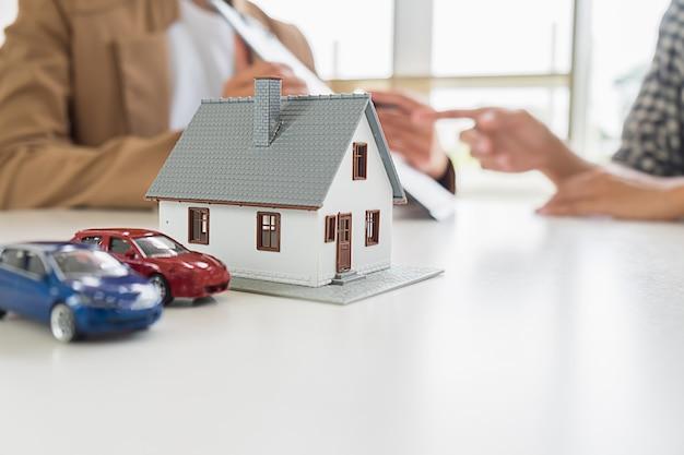 Modelo de casa con agente inmobiliario y cliente discutiendo por contrato para comprar casa Foto Premium