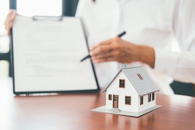 Modelo de casa con agente inmobiliario y cliente discutiendo sobre el contrato para comprar casa, seguro o préstamo inmobiliario. Foto Premium