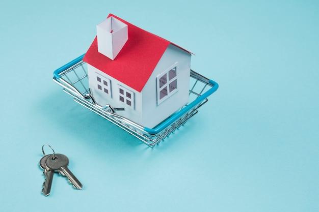 Modelo de casa en cesto metálico y llaves sobre fondo azul. Foto gratis