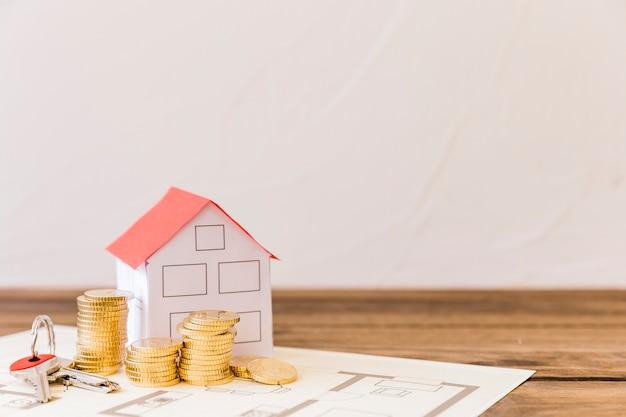 Modelo de la casa, llave y monedas apiladas en blueprint Foto gratis