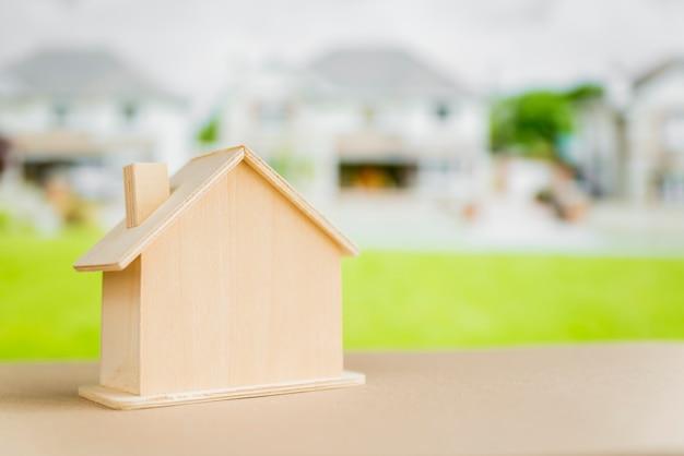 Modelo de casa en miniatura en mesa frente a casas suburbanas Foto gratis