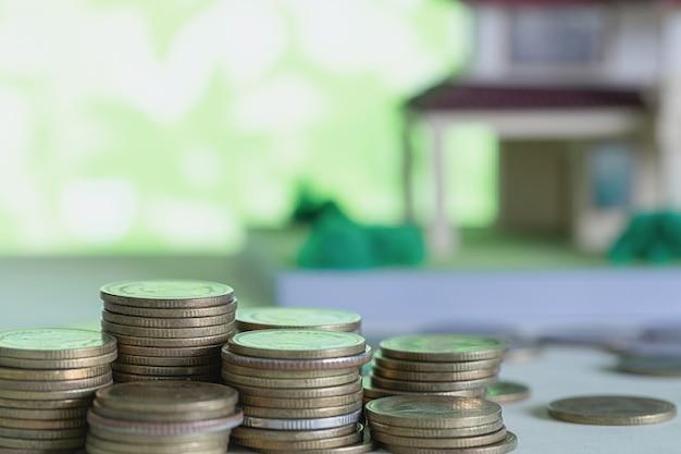 Modelo de casa con monedas en mesa de madera. Foto gratis