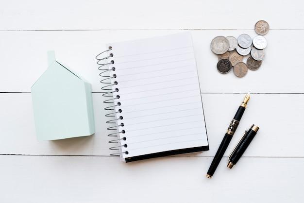Modelo de casa de papel azul; diario en espiral; monedas y pluma estilográfica negra con tapa abierta sobre mesa blanca Foto gratis