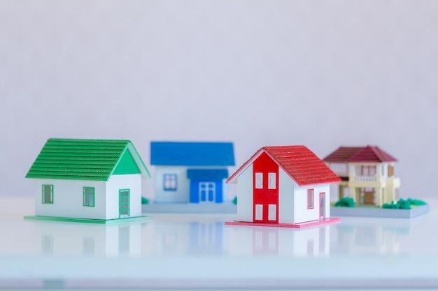 Modelo de casa pintada de blanco bajo el techo de tejas. Foto gratis