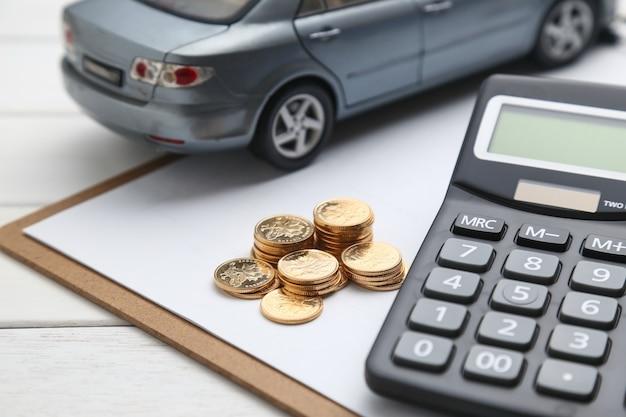 Modelo de coche, calculadora y monedas en la mesa blanca Foto gratis