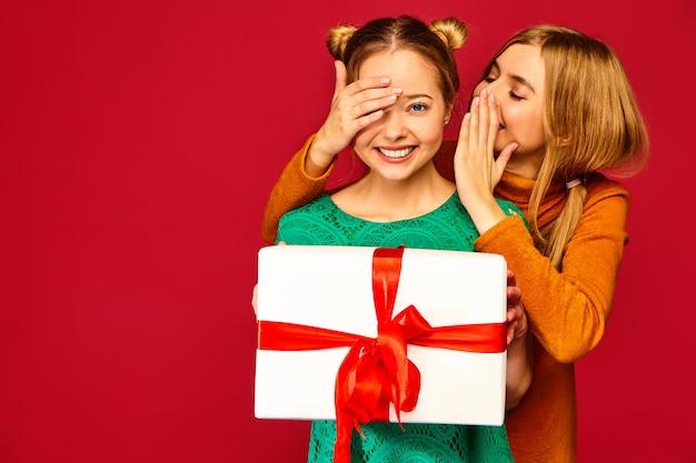 Modelo cubriendo los ojos de su amiga y dándole una gran caja de regalo y un secreto secreto Foto gratis