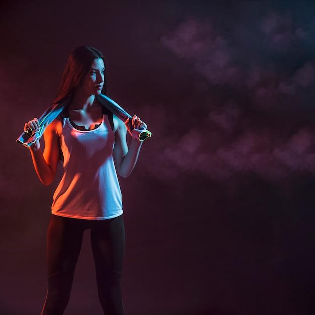 Modelo deportivo con toalla en la oscuridad Foto gratis