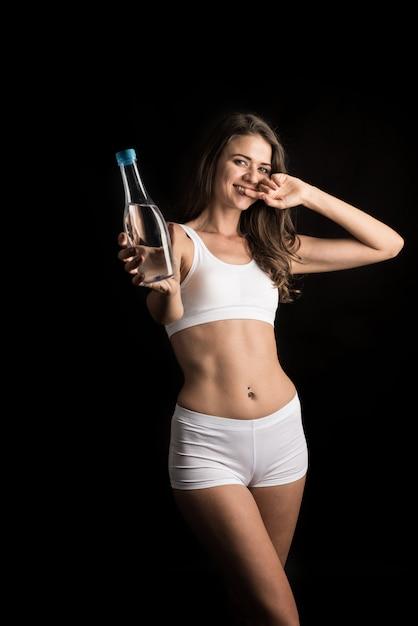 Modelo femenino de la aptitud que sostiene una botella de agua Foto gratis
