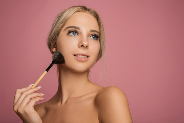 Modelo femenino con pincel de maquillaje Foto gratis