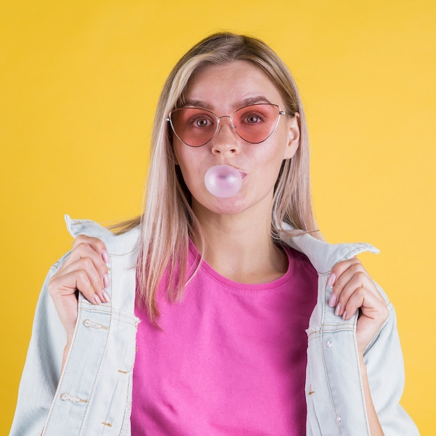 Modelo femenino que sopla chicle Foto gratis