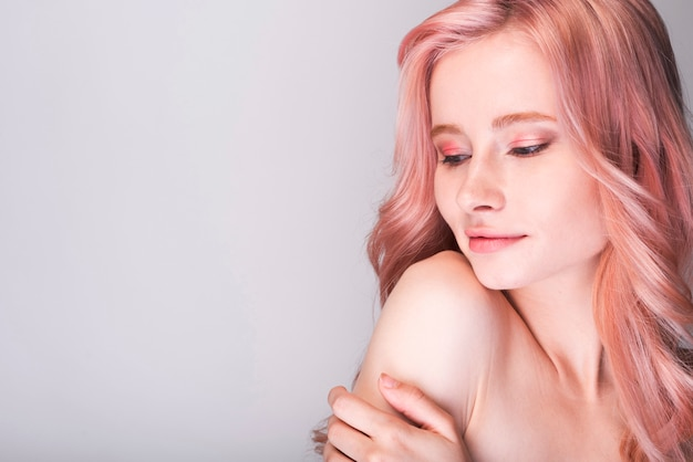 Modelo femenino sosteniendo su brazo con espacio de copia Foto gratis