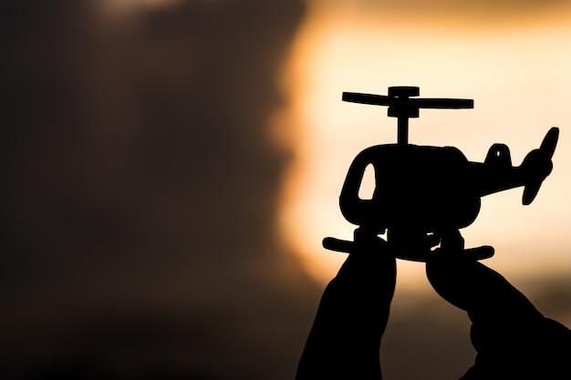 Modelo de helicóptero en las manos de la silueta en el cielo la luz del sol. Foto Premium